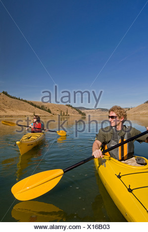 A young couple enjoys a spectacular day of kayaking on Trapp Lake, just south of Kamloops, British Columbia, Canada - Stock Photo