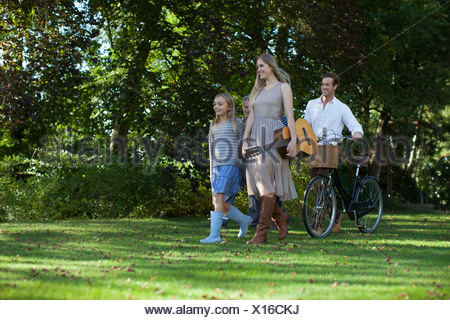 Multi-generation family with bicycle and guitar in orchard - Stock Photo