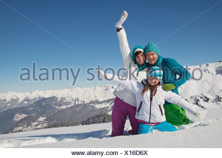 Couple and daughter in ski wear, playing in snow - Stock Photo