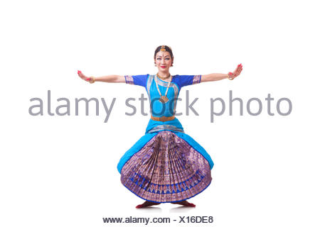 Full length of dancer with arms outstretched performing Bharatanatyam against white background - Stock Photo