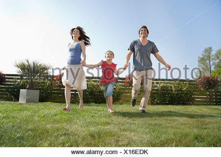 Parents and daughter holding hands and running in grass - Stock Photo