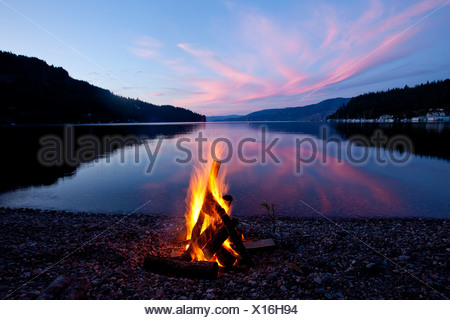 Campfire with sunset reflected on the lake in Idaho. - Stock Photo