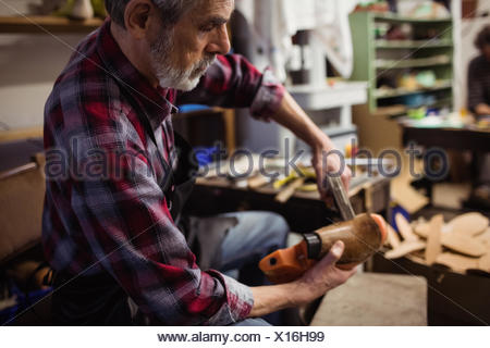 Profile view of cobbler stapling a shoe - Stock Photo
