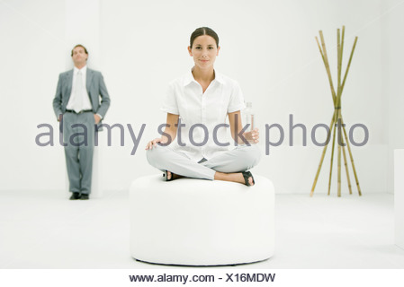 Professional woman sitting on ottoman, holding water bottle, businessman and bamboo in background - Stock Photo