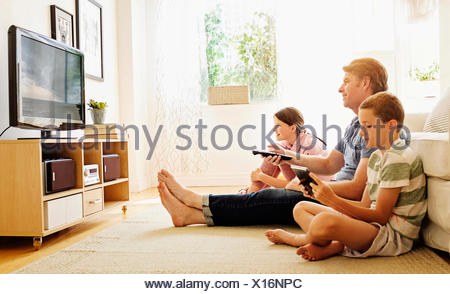 Children (8-9, 10-11) watching TV with their father - Stock Photo
