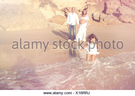 Pregnant woman with husband and daughter on beach - Stock Photo