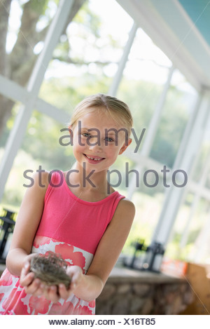 A young girl in a kitchen wearing a pink dress. Holding a bird's nest. - Stock Photo