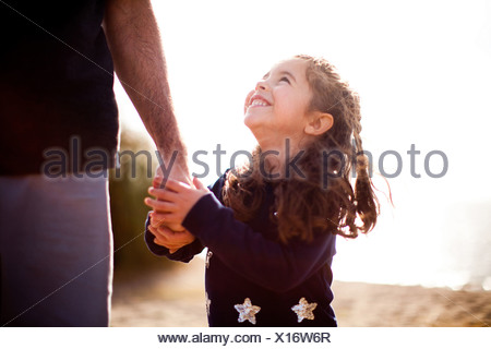 Girl holding father's hand, looking up - Stock Photo