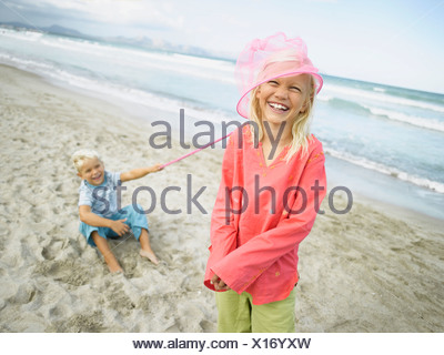 Girl and a boy playing on the beach - Stock Photo