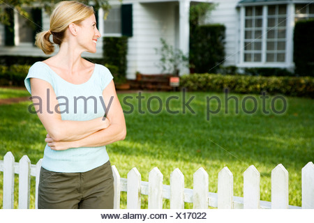 Woman standing by the garden fence outside her new home - Stock Photo
