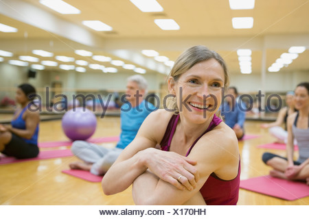 Smiling woman on yoga mat in exercise class - Stock Photo