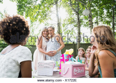 Mother and pregnant daughter hugging backyard baby shower - Stock Photo
