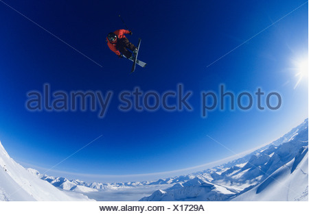 Skier jumping, against blue sky - Stock Photo