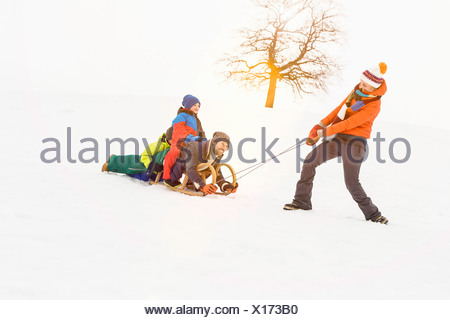 Woman pulling toboggan in snow with man and two boys - Stock Photo