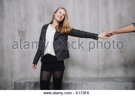 Couple in front of concrete wall, woman holding hand of man - Stock Photo