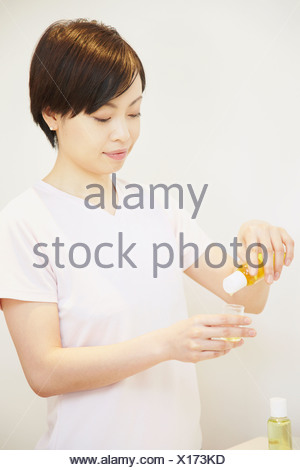 Woman pouring aromatherapy oil into container - Stock Photo