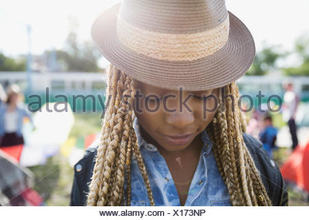 Close up portrait young woman with blonde braids wearing hat looking down at summer music festival campsite - Stock Photo