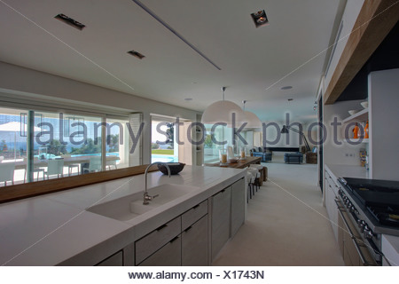 Modern white galley kitchen with chrome stools at breakfast bar set ...