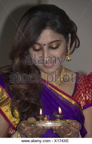 Hindu Indian lady in sari doing the aarti - Stock Photo