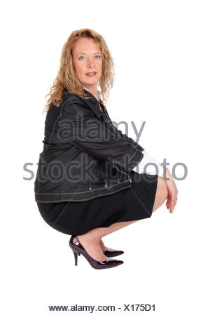 Lovely woman crouching on floor. - Stock Photo