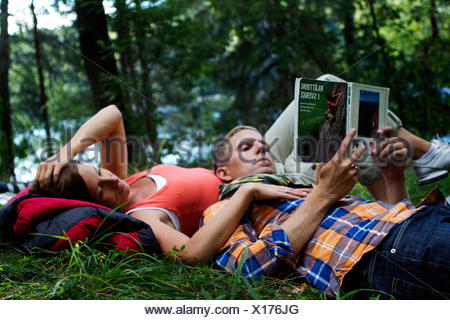Sweden, Ostergotland, Agelsjon, Hikers lying on grass and reading guidebook - Stock Photo