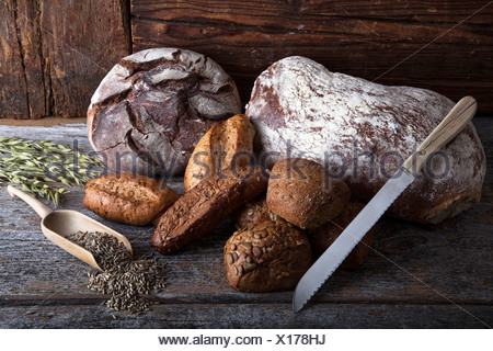 Bread loaves, rolls and a bread knife, rye grain and ears of corn on a rustic wooden surface - Stock Photo