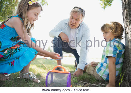 Kids catching bugs with their grandfather - Stock Photo
