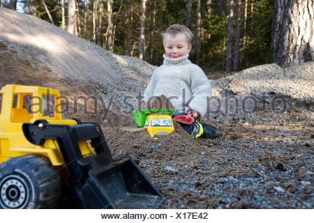 Little boy sitting in sandbox with cropped toy backhoe in foreground - Stock Photo