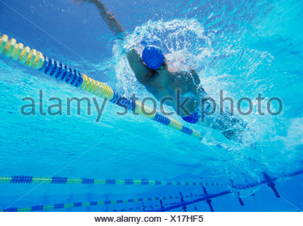 Young professional male thlete doing backstroke in swimming pool - Stock Photo