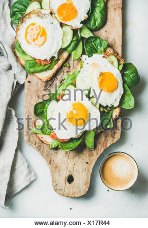 Healthy breakfast sandwiches and cup of coffee. Bread toasts with fried eggs and fresh vegetables on rustic wooden board over grey marble background,  - Stock Photo