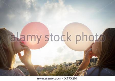 Girls blowing balloons - Stock Photo