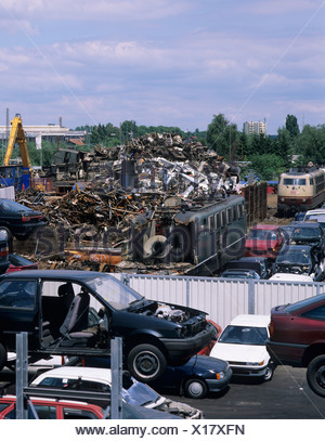 View of a scrapyard, car chassis, electric trains and old metal parts - Stock Photo
