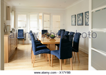 Upholstered Blue Chairs And Wooden Table In Pastel Yellow Kitchen