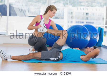 Female trainer helping man with his exercises at gym - Stock Photo