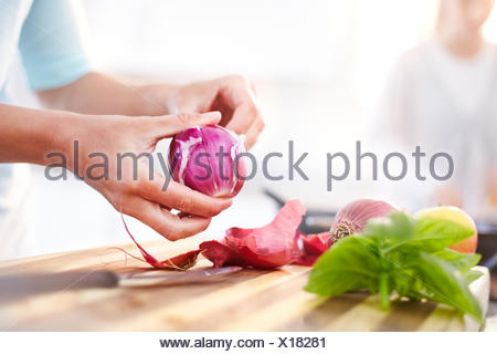 Woman peeling red onion in kitchen - Stock Photo