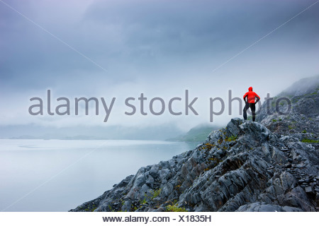 A lone hiker stands on a rocky outcropping overlooking Shoup Bay State Marine Park, Prince William Sound, Alaska - Stock Photo