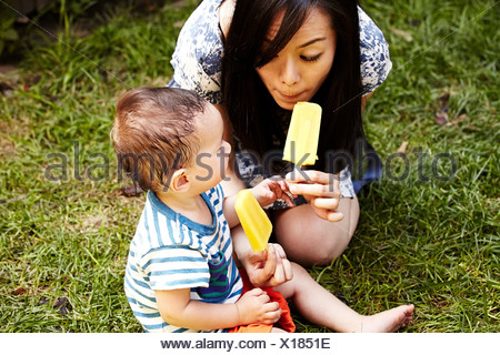 Mother and son sitting on grass eating ice lollies - Stock Photo