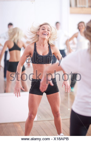 Young woman jumping in aerobic class - Stock Photo