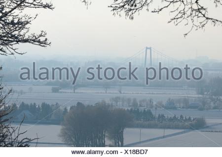 Hangbrug van Emmerich over de Rijn in een besneeuwd landschap, dit is de hangbrug die het dichtst bij Nederland ligt; Suspension-bridge of Emmerich over the river Rhine in a snow covered landscape - Stock Photo