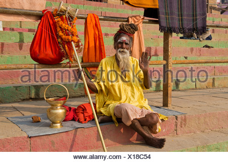 Elderly Sadhu, holy man or wandering ascetic sitting on a blanket on the steps on the bank of the Ganges River with various - Stock Photo