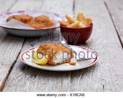 Breaded chunky cod with bowl of french fries on wooden table - Stock Photo