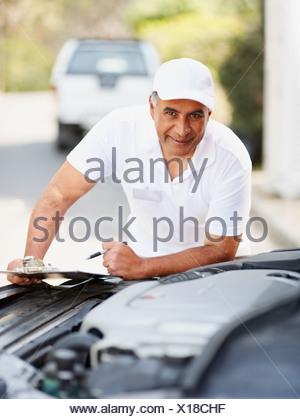 Man looking at car's engine - Stock Photo