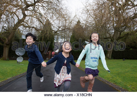 Young friends running through park holding hands - Stock Photo