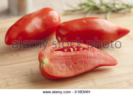 Whole and half fresh Cornue des Andes tomatoes. - Stock Photo