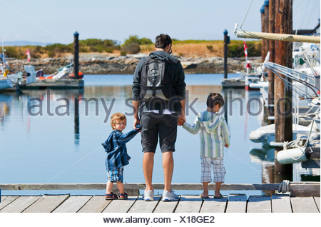 A Father With Two Sons Standing On A Dock Looking Into The Water; Langley, British Columbia, Canada - Stock Photo