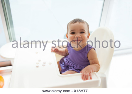 Baby girl sitting in high chair smiling, portrait - Stock Photo