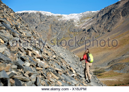Woman hiking on the Crow Pass Trail along a steep rocky incline, Chugach Mountains, Southcentral Alaska, Autumn - Stock Photo
