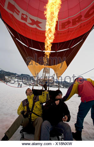 hot-air balloon standing on snow field with two men on bord while being fired for the start, Germany, Bavaria, Allgaeu, Oberstdorf - Stock Photo