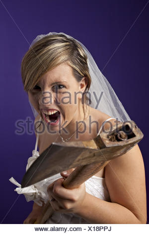 angry young bride with an axe on a dark blue background - Stock Photo