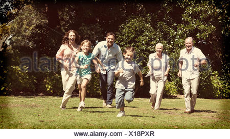 Happy multi generation family running towards camera - Stock Photo